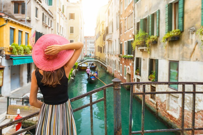 A woman in a pink hat stands on a bridge over a canal in Venice watching a gondola.