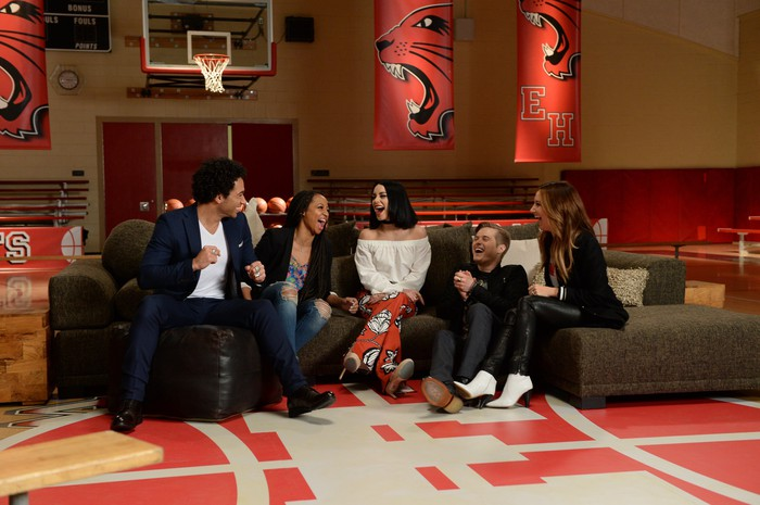 """The stars of Disney's """"High School Musical"""" at a reunion smiling and laughing, while sitting on a couch in a high school gymnasium."""