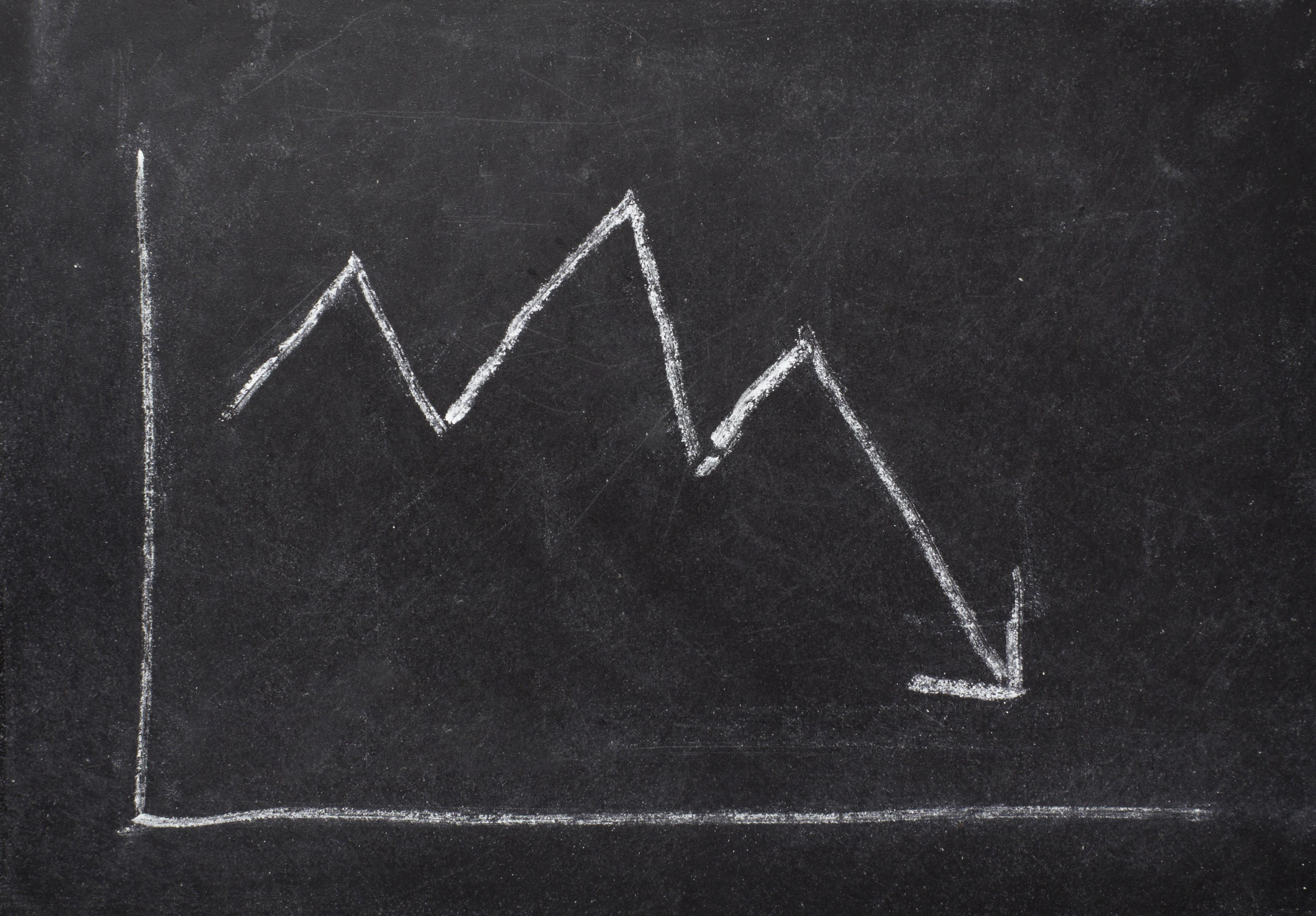 A chalkboard sketch of a chart showing a white arrow falling.