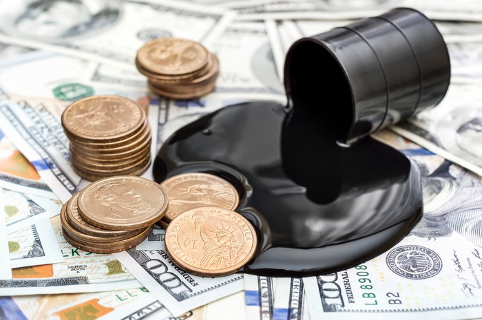A miniature barrel of oil spilling on a pile of dollars and coins.