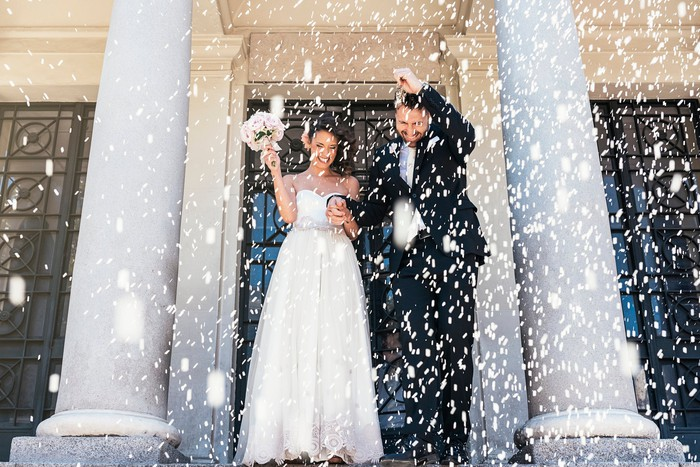 Confetti being thrown at newlyweds exiting a church.