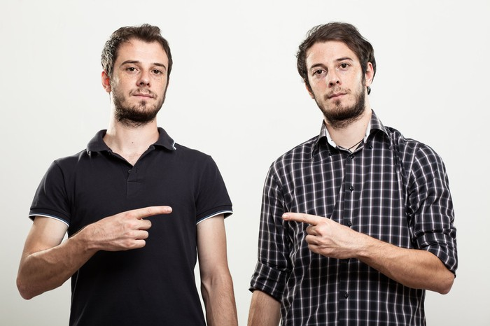 A pair of twin young men pointing at each other
