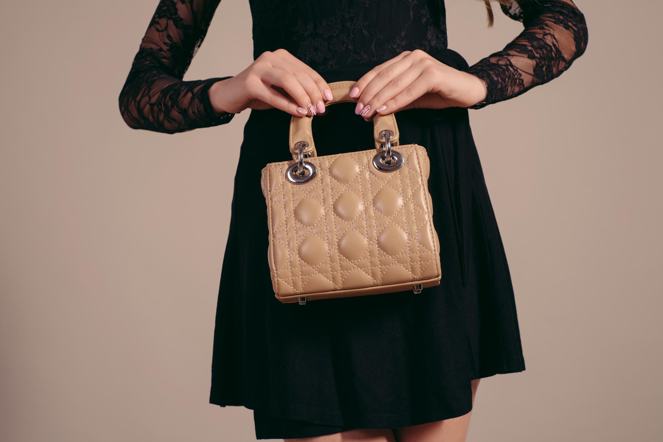 Woman in stylish black dress holding luxury handbag.
