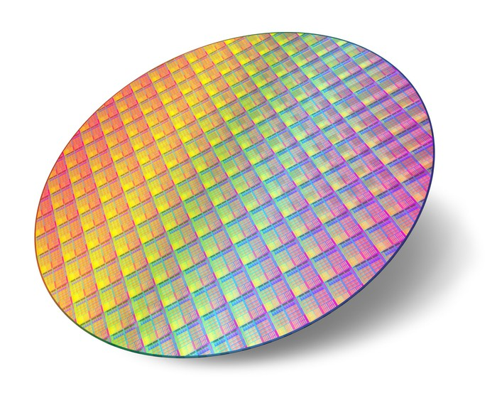 An uncut circular wafer of semiconductor chips in the making.