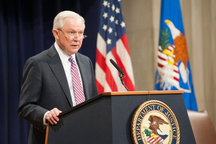 Former Attorney General Jeff Sessions speaking to an audience from behind a podium.