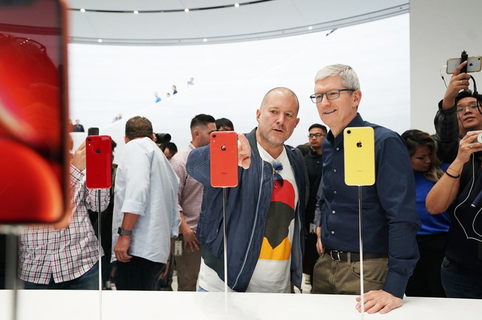 Apple executives Jony Ive and Tim Cook looking at red and yellow iPhone XR smartphones