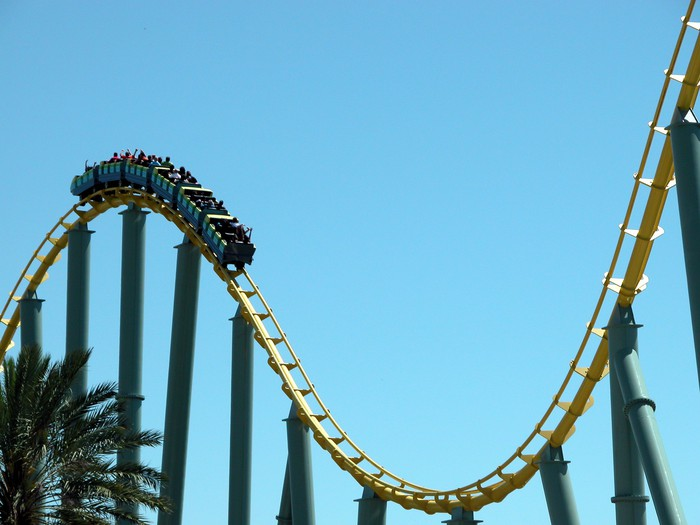 A blue roller coaster about to go down a decline in the tracks, with a blue sky in background.