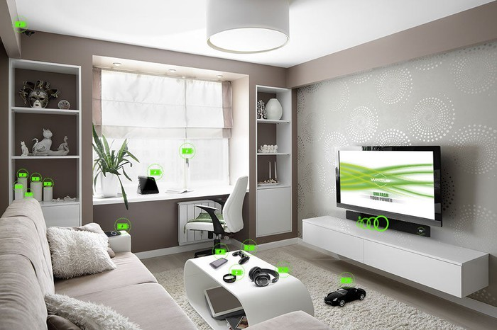 Contemporary living room with green wireless charging icons above each of its electronic devices.