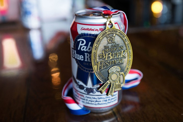 Can of Pabst Blue Ribbon on a wood table with a beer festival medal hanging on it.