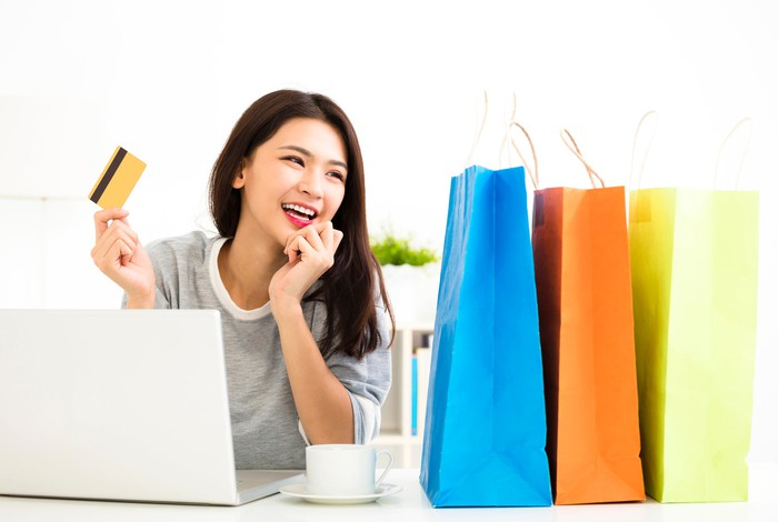 An Asian woman holding a credit card in her hand as she sits in front of a laptop, a cup of coffee, and three colorful shopping bags