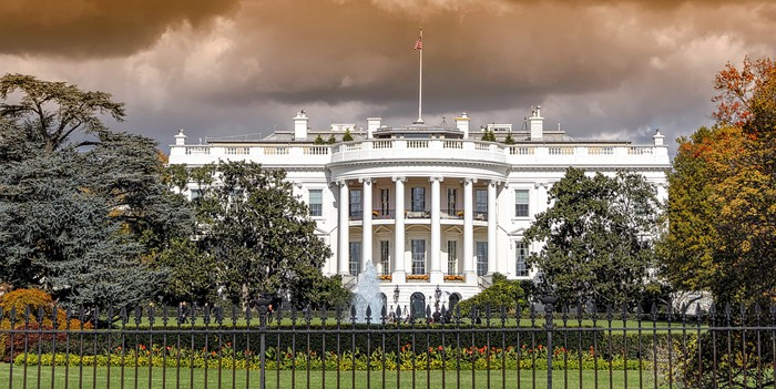 The White House with storm clouds in background.