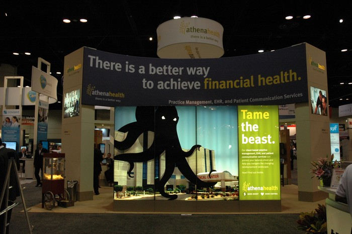 Booth at a conference center with Athenahealth exhibits and displays.