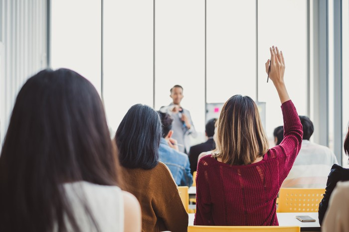 A woman raising her hand in class.