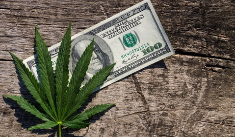 marijuana leaf next to money on a brown desk top GettyImages-698117236