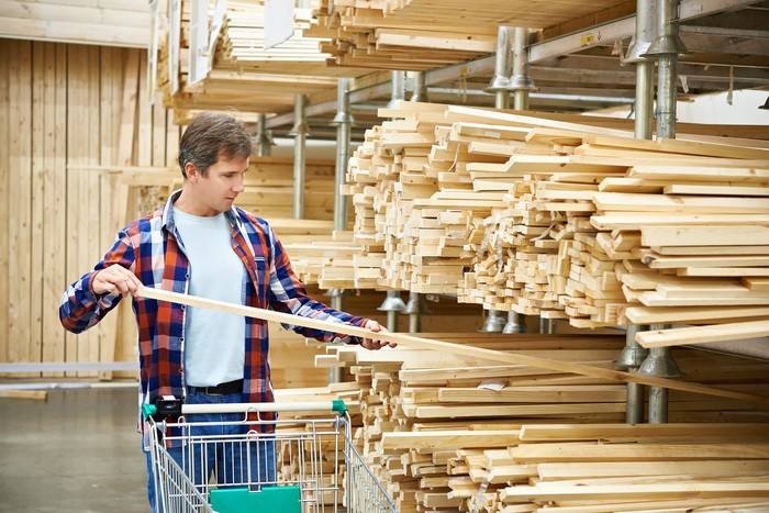 A man with a shopping cart looks over thin pieces of lumber.