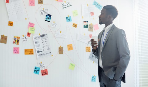 man looking at wall full of info getty
