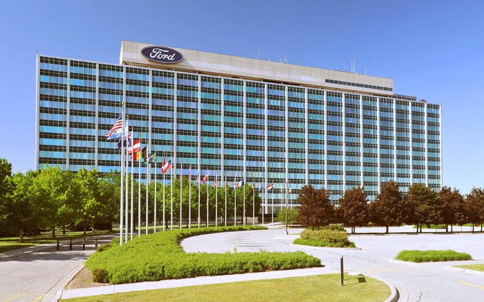 Ford's headquarters, a 12-story blue-glass-faced office building, viewed from a flag-lined driveway in front.