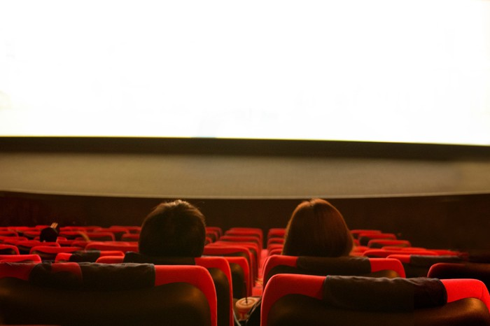 The back of two people's heads in a movie theater, with empty seats around them.