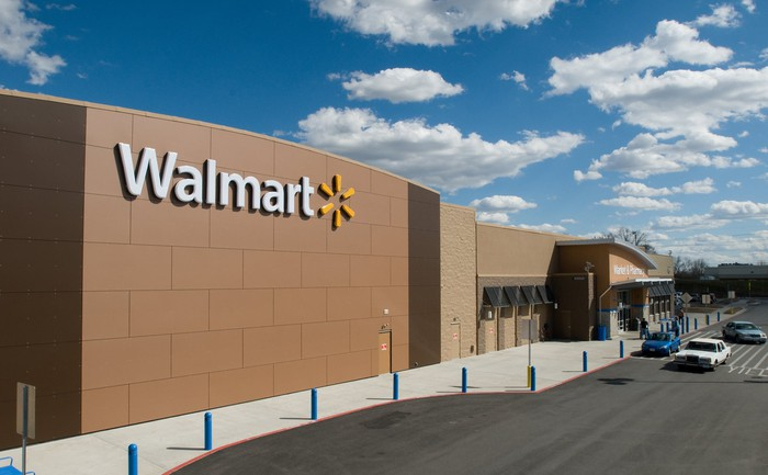 A Walmart storefront against a blue sky with white, fluffy clouds.