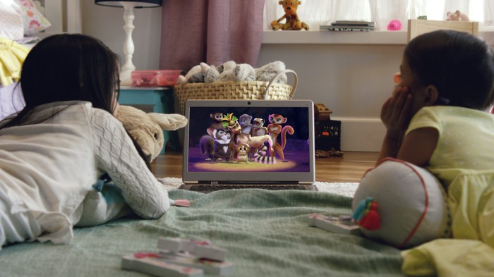 Two kids watching a video on a laptop in a bedroom.