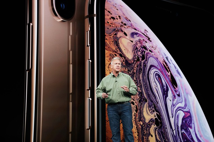 Apple marketing chief Phil Schiller on stage with gold iPhone XS/XS Max smartphone images behind him.