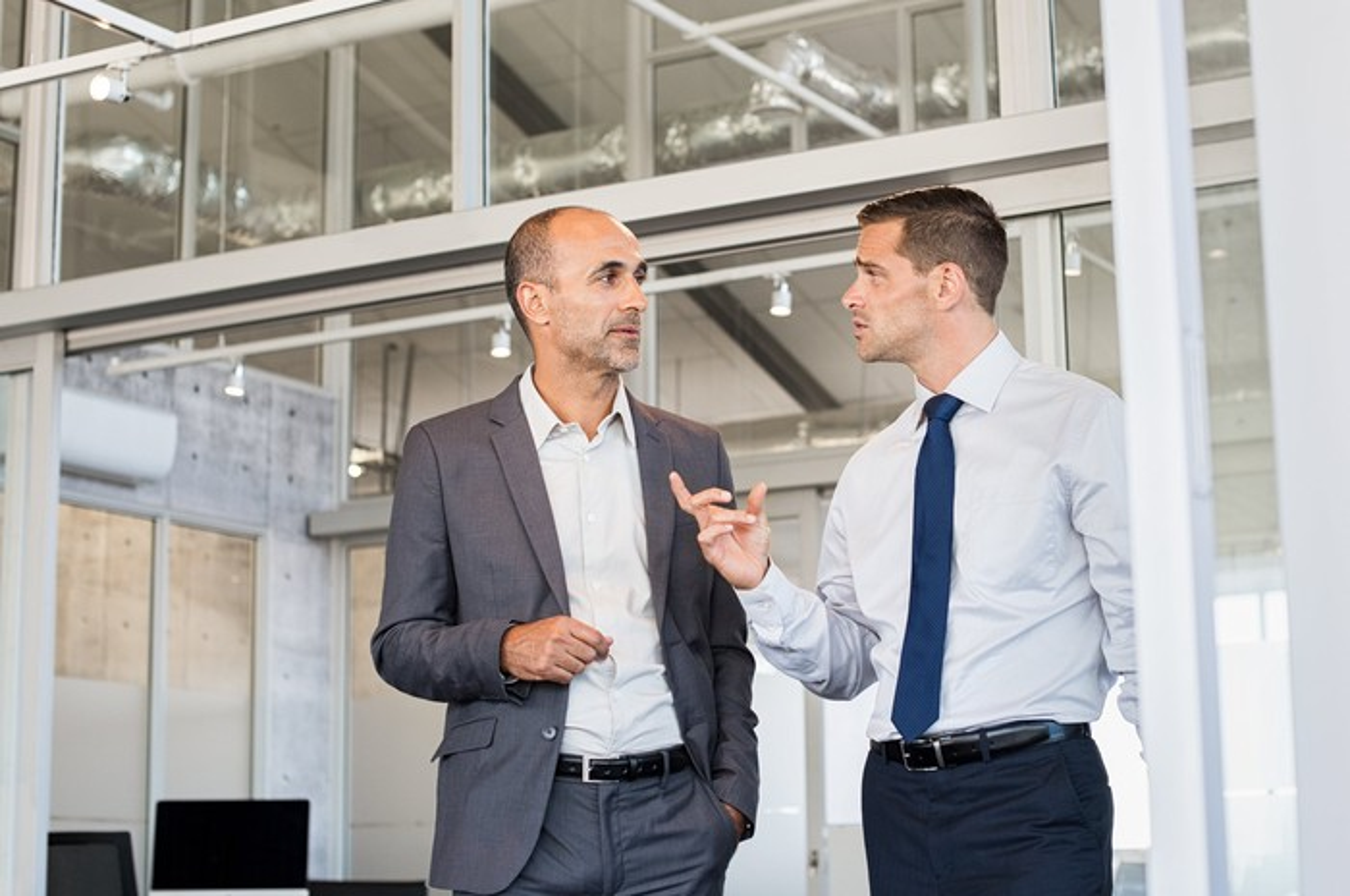 Two men in professional attire having a discussion.