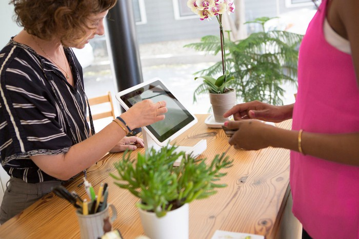 A merchant helps a woman use Square's digital register at checkout in a store.