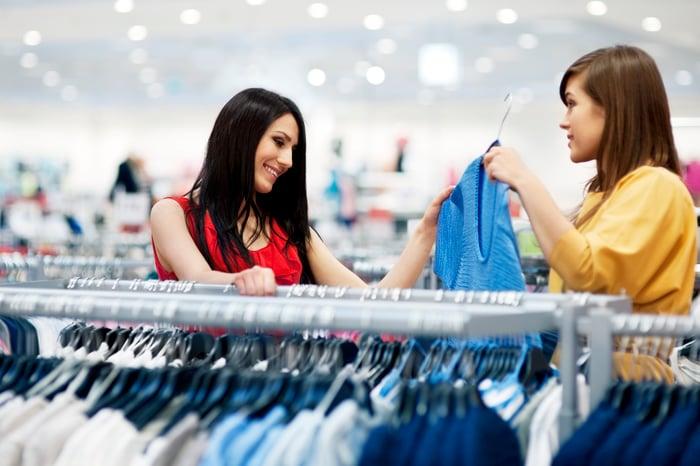 Two young women shopping for shirts.