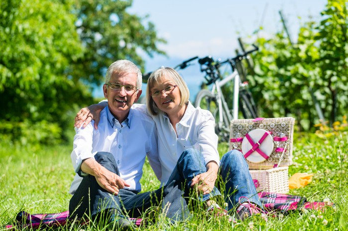 Senior couple with arms around each other sitting on grass in front of picnic basket