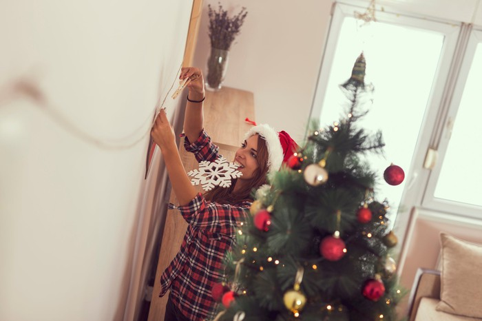 Woman hanging lights while standing next to a Christmas tree.