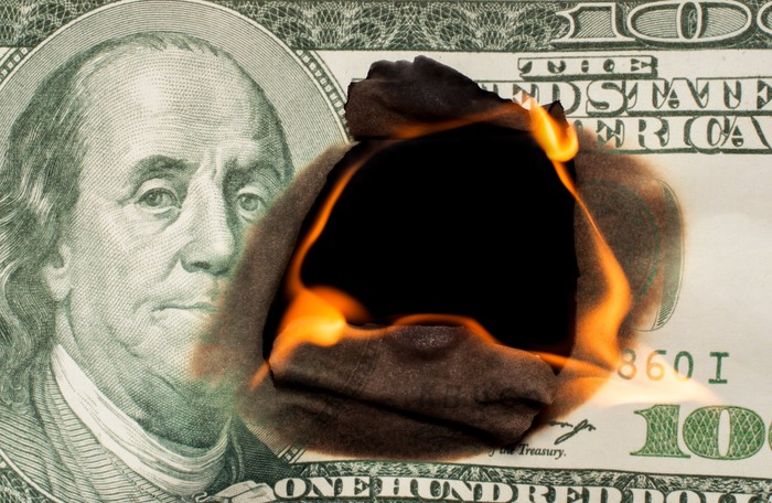 A fire burning from the center outward of a hundred dollar bill.
