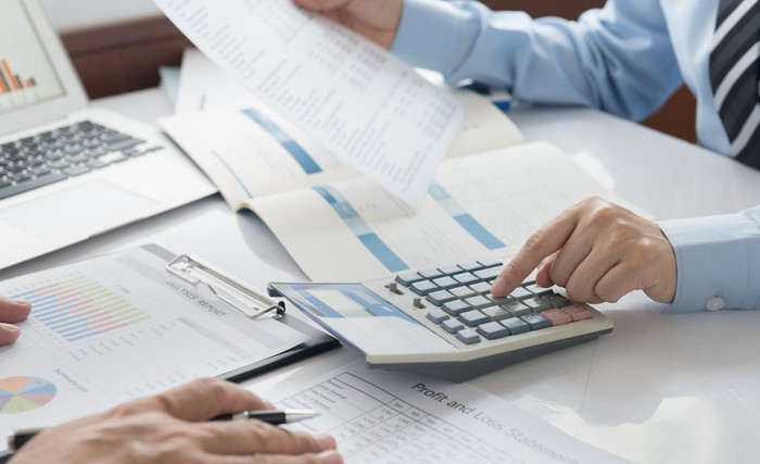 Workers use calculators and spreadsheets to crunch numbers around a conference table.