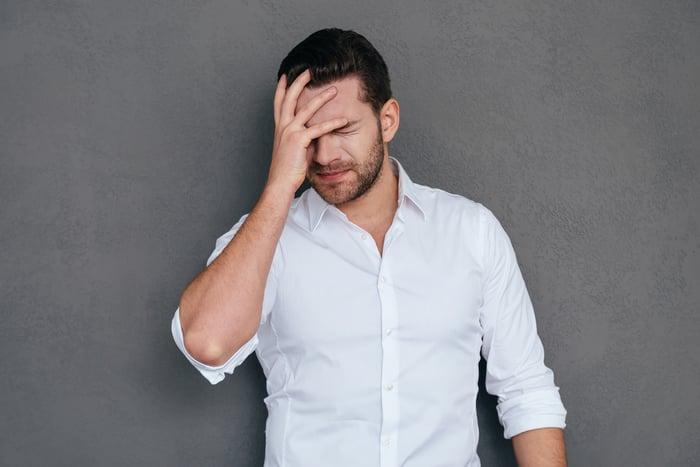 Man in a white shirt facepalming