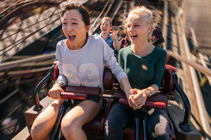 Two girls with their mouths open riding a roller coaster.