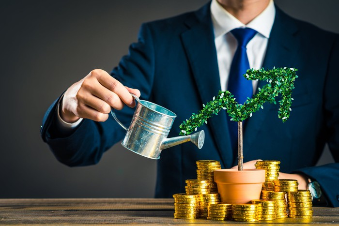 Businessman watering plant shaped like an upward-pointing arrow with stacks of gold coins surrounding it.