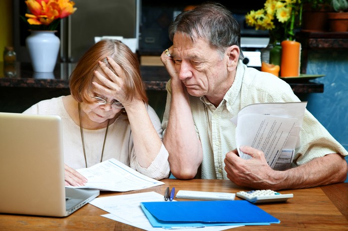 Senior couple sitting in front of a computer with papers on the desk and in their hands and looking worried.