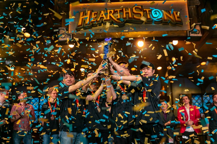 Professional Hearthstone players holding up a trophy with confetti falling as they celebrate a victory at an esport event.