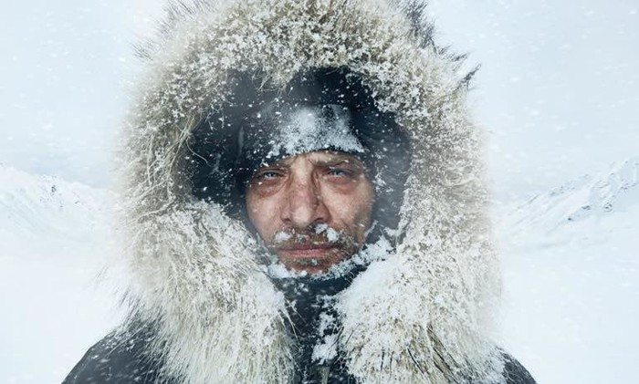 A man's face is coated with ice and snow under a furry hood.