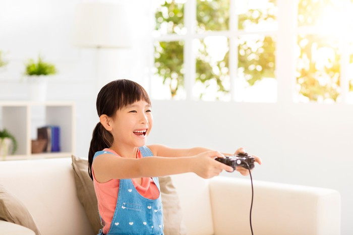 Laughing little girl playing video games on sofa.