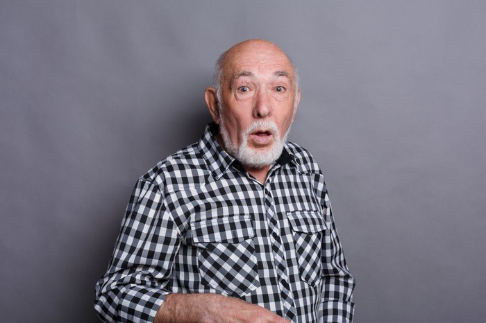Older man with surprised expression against gray background