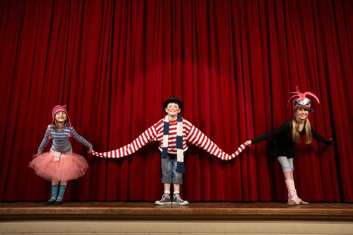 Children in clown costumes making curtain call.