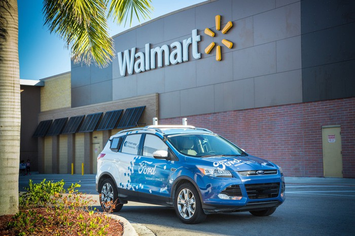 A Ford Escape, a compact SUV, with blue and white Ford graphics and visible self-driving sensor hardware, in front of a Walmart store