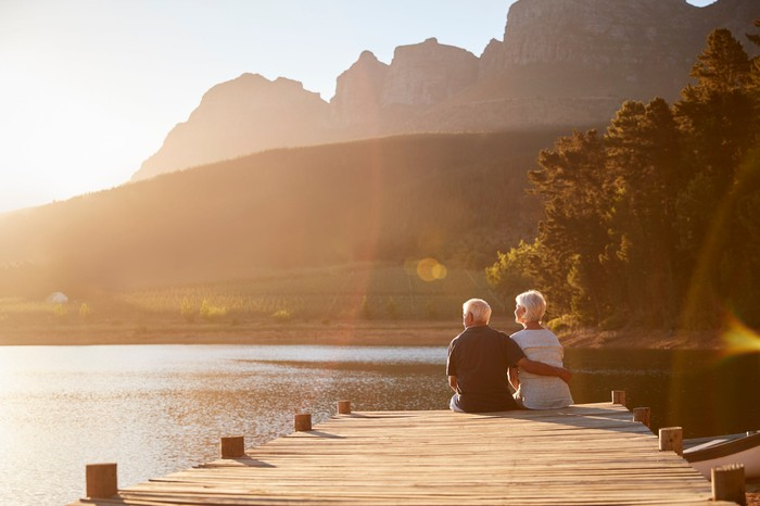 A retired couple sit at the end of a dock on a lake at sunset.