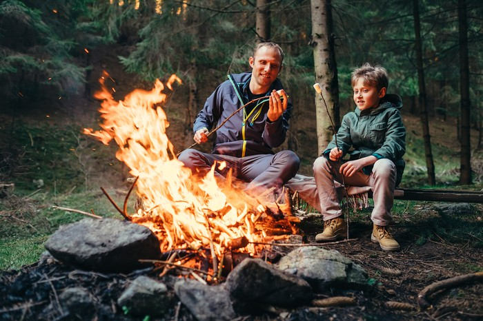Dad and son toasting marshmallows at a campfire