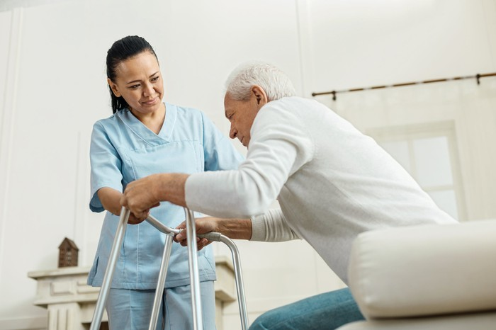 Nurse assisting an elderly patient in standing up.