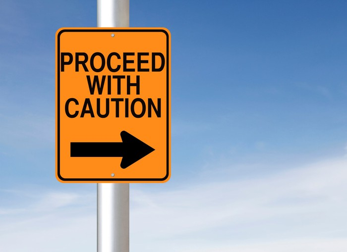road sign that says proceed with caution and has arrow pointing to the right
