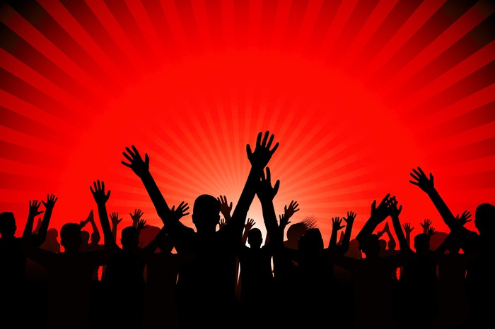 A large crowd of people with their hands in the air, silhouetted against a red light in the background.
