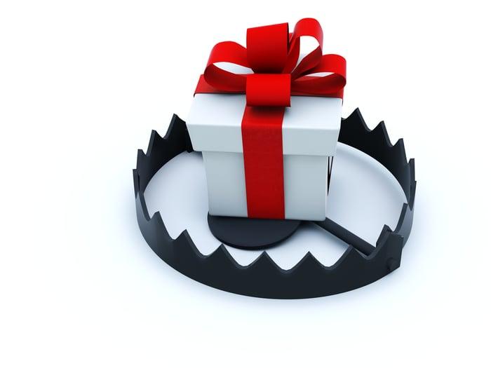 A gift box sits inside a bear trap.