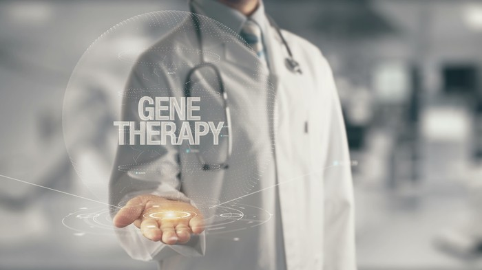 """Physician with hand held out and graphic with words """"Gene Therapy"""" appearing in foreground"""