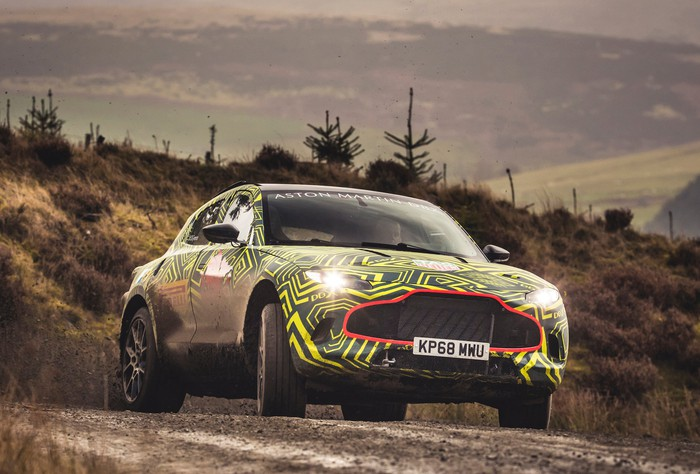 A prototype Aston Martin DBX, a high-performance luxury SUV, covered in yellow and black camouflage, in a rugged hilly setting.